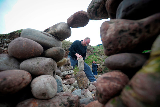Competitors take part in the European Stone Stacking Championships 2018 in Dunbar, Scotland, on April 22, 2018. The European Stone Stacking Championships are Europe's largest championships for all Stone Stacking and Rock Balancing artists and practitioners. The overall winner of the European Stone Stacking Championship will receive financial support for flights to the World Stone Balance Championship in Llano, Texas the following year. (Photo by Andy Buchanan/AFP Photo)