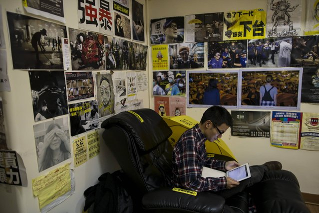 Banners and posters collected from the Occupy zone adorn the wall behind Chinese traveller David King, as he uses an iPad at a guesthouse in Hong Kong December 30, 2014. (Photo by Tyrone Siu/Reuters)