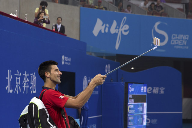 Novak Djokovic of Serbia uses a mobile phone to take a selfie with spectators after winning the first round men's singles match against Simone Bolelli of Italy in the China Open tennis tournament at the National Tennis Stadium in Beijing, Tuesday, October 6, 2015. (Photo by Andy Wong/AP Photo)