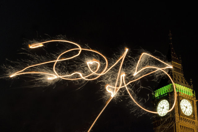 "Using a long time exposure an unseen person writes ""2015"" using a sparkler in front of the Queen Elizabeth Tower and The Houses of Parliament ahead of the new year fireworks in central London, England, 31 December 2014. Around 100,000 people are expected to take part in the festivities on the bank of the river Thames. (Photo by Hannah Mckay/EPA)"