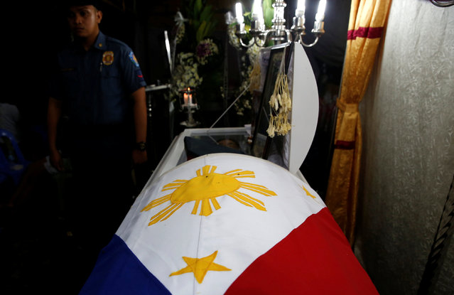 A policeman stands guard beside the flag-draped coffin of fellow officer Rancel Cruz, whom police investigators said was shot dead by a drug addict, in Manila, Philippines October 19, 2016. (Photo by Erik De Castro/Reuters)