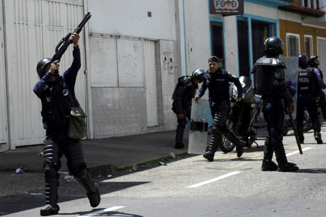 A riot police officer fires into the air during clashes with opposition supporters in a rally to demand a referendum to remove President Nicolas Maduro in San Cristobal, Venezuela October 24, 2016. (Photo by Carlos Eduardo Ramirez/Reuters)