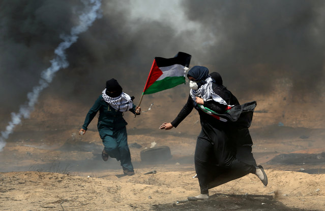 Female demonstrators run for cover from tear gas fired by Israeli forces during a protest where Palestinians demand the right to return to their homeland, at the Israel-Gaza border in the southern Gaza Strip, May 11, 2018. (Photo by Ibraheem Abu Mustafa/Reuters)