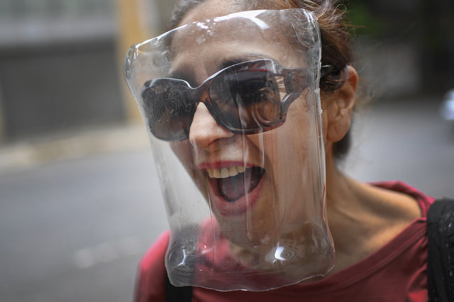 A woman wears a makeshift face shield made from a plastic bottle container as a precaution against the new coronavirus, in Caracas, Venezuela, Saturday, April 18, 2020. (Photo by Matias Delacroix/AP Photo)