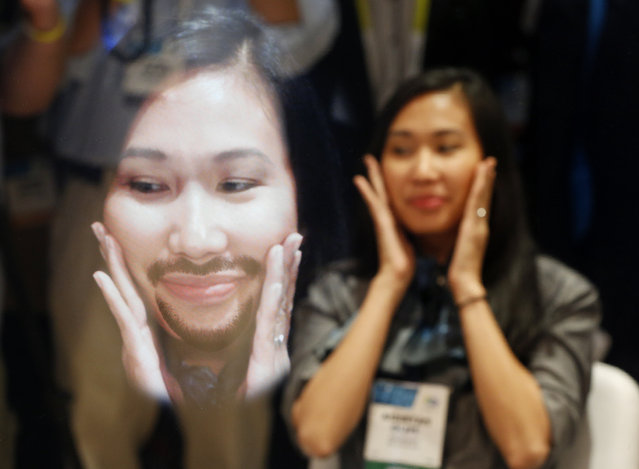 A woman reacts as a goatee is superimposed on an image of her face in the Future Mirror at the Panasonic booth during the International CES Tuesday, January 6, 2015, in Las Vegas. A camera in the mirror allows the Future Mirror to display a moving image of your face with added facial hair or makeup in real time. (Photo by John Locher/AP Photo)
