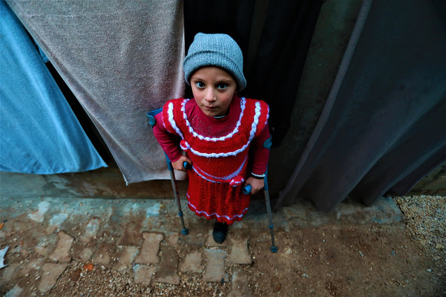 Six-year-old Esra Salih, who fled Deash attacks and took refuge in Idlib and lost her left leg in an attack of Assad Regime within the Syrian Civil War, poses for a photo with her crutches in Idlib, Syria on December 20, 2020. Esra Salih waits for the day to reach a prosthesis leg. (Photo by Bekir Kasim/Anadolu Agency via Getty Images)