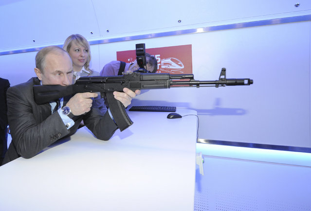"""Vladimir Putin takes aim with a model assault rifle at an electronic shooting range during his visit to a research facility of national railway company """"Russian Railways"""" in Moscow April 26, 2012. (Photo by Alexei Druzhinin/Reuters/RIA Novosti)"""