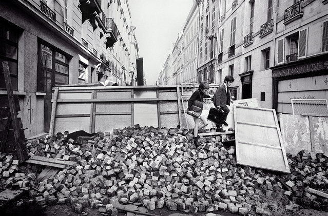 Rue de l'Universite. Although universities were closed during the student riots, elementary schools remained open and young children attended classes, climbing over paving stones at a barricade erected by students, Rue de l'Universite, Paris, France, June 11, 1968. (Photo by Gökşin Sipahioğlu/SIPA Press)