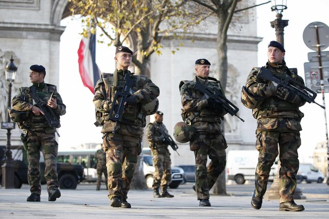 """French soldiers patrol in front of the Arc de Triomphe on the Champs Elysees avenue in Paris, France, as part of France's national security alert system """"Sentinelle"""" after Paris deadly attacks November 27, 2015. (Photo by Charles Platiau/Reuters)"""