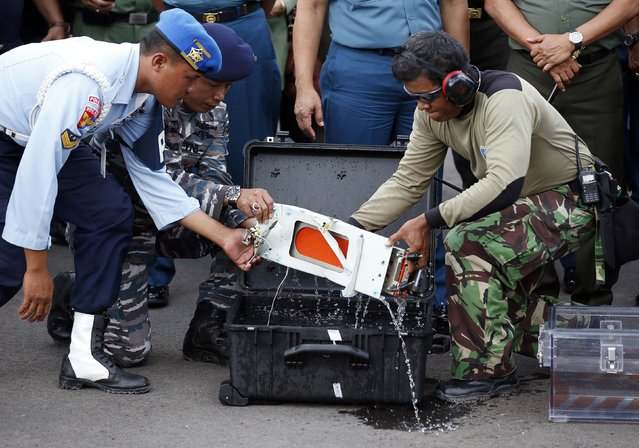 The flight data recorder of AirAsia QZ8501 is lifted out of a carrying case at the airbase in Pangkalan Bun, Central Kalimantan January 12, 2015. (Photo by Darren Whiteside/Reuters)