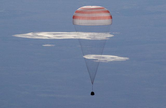 The Soyuz MS-07 capsule carrying the crew of Norishige Kanai of Japan, Anton Shkaplerov of Russia, and Scott Tingle of the U.S. descends beneath a parachute just before landing in a remote area outside the town of Dzhezkazgan (Zhezkazgan), Kazakhstan June 3, 2018. (Photo by Dmitri Lovetsky/Pool via Reuters)
