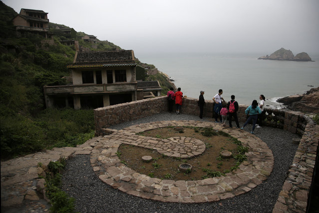 This May 19, 2018, photo shows tourists next to an abandoned building in the former fishing village of Houtouwan on the remote island of Shengshan, 90 kilometers off the coast of Shanghai. (Photo by Sam McNeil/AP Photo)