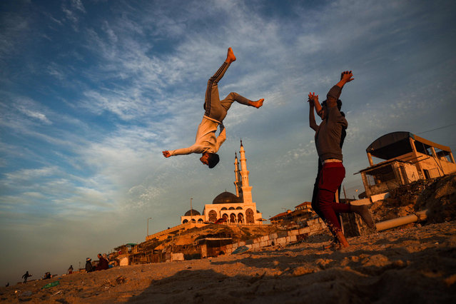 Palestinian children practise parkour along a beach in Gaza City at sunset on January 27, 2021. (Photo by Mohammed Abed/AFP Photo)