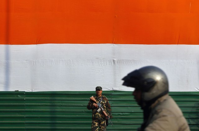An Indian security personnel stands guard as a motorist passes by near India Gate, ahead of the Republic Day parade in New Delhi January 23, 2015. (Photo by Anindito Mukherjee/Reuters)