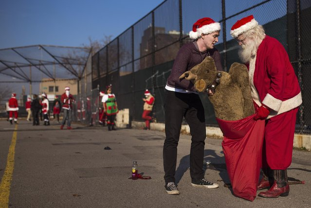 Revelers dressed in holiday theme costumes gather in the park as they participate in SantaCon in the borough of Brooklyn in New York Saturday, December 12, 2015. (Photo by Andres Kudacki/AP Photo)