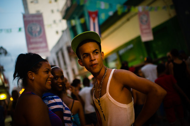 Luis Angel Estrada, 17, right, wears a New York hat.  In the neighborhood of Central Havana, a block hosted a birthday party for Fidel Castro on Thursday, August 13, 2015. As loud music plays, girls dance in the street. (Photo by Sarah L. Voisin/The Washington Post)