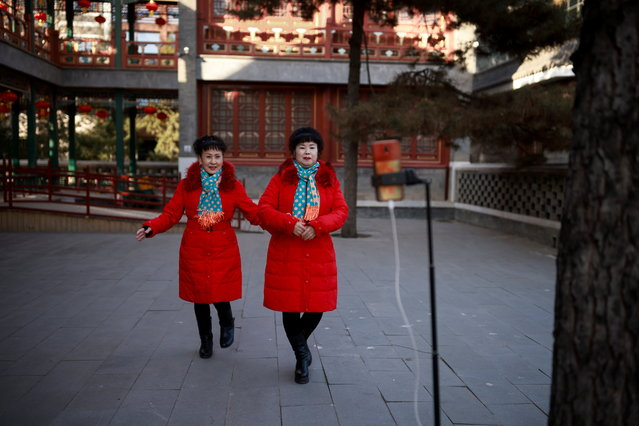 Women record a synchronised dance on their phone in Daguanyuan Park as China celebrates Lunar New Year of the Ox following an outbreak of the coronavirus disease (COVID-19) in Beijing, China, February 15, 2021. (Photo by Thomas Peter/Reuters)