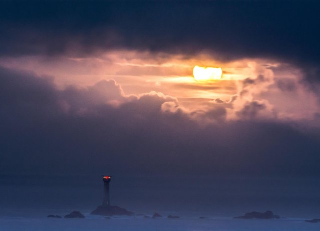The Supermoon sets over the Longships lighthouse at Lands End, Cornwall, UK on November 14, 2016, before it's final rising later on today. Clouds are threatening to obscure the view in much of the south west. (Photo by Simon Maycock/Alamy Live News)