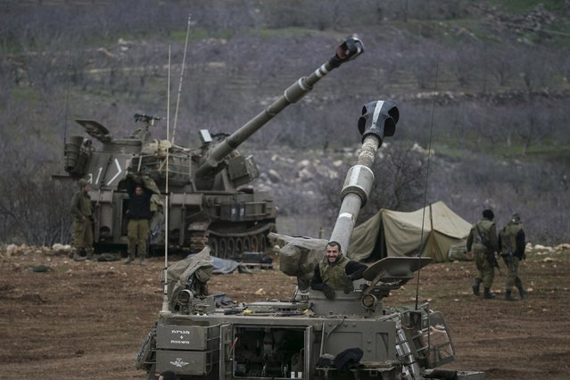 Israeli soldiers are seen next to mobile artillery units near the border with Syria in the Golan Heights January 27, 2015. At least two rockets from Syria hit the Israeli-occupied Golan Heights on Tuesday and Israel returned fire, the military said, nine days after an Israeli air strike in Syria killed an Iranian general and several Lebanese Hezbollah guerrillas. (Photo by Baz Ratner/Reuters)