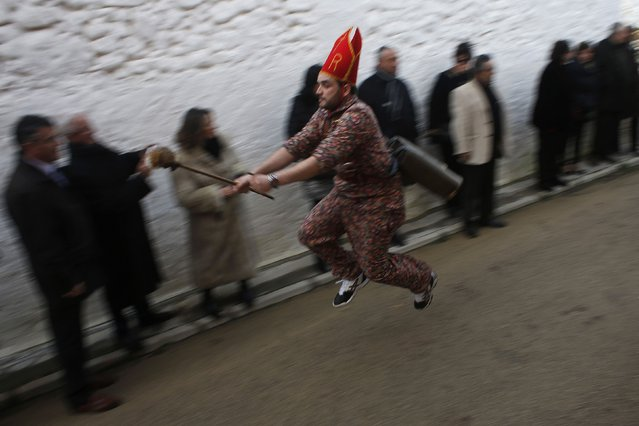 "A believer dressed as a ""diablo"" (devil) jumps at the San Blas' (Saint Blaise) procession during the ""Endiablada"" festival in Almonacid del Marquesado, in central Spain February 3, 2015. In the ""Endiablada"", an undated traditional festival in honour of the Candelaria Virgin and San Blas. (Photo by Susana Vera/Reuters)"