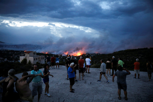 People watch a wildfire raging in the town of Rafina, near Athens, Greece, July 23, 2018. (Photo by Alkis Konstantinidis/Reuters)