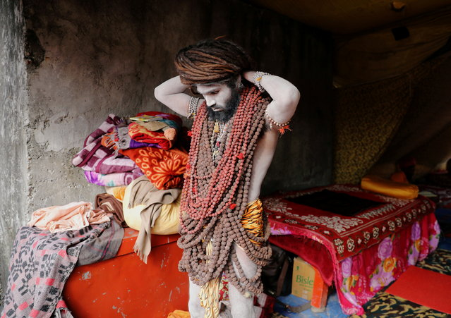 """A Naga Sadhu or Hindu holy man adjusts the beads around his neck ahead of the first Shahi Snan at """"Kumbh Mela"""" or the Pitcher Festival, in Haridwar, India, March 10, 2021. (Photo by Anushree Fadnavis/Reuters)"""