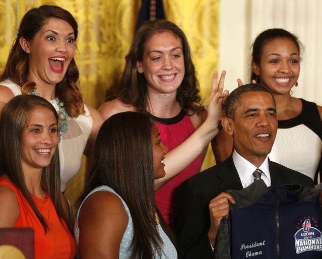 Stefanie Dolson (top left), NCAA women's basketball 2013 national champions player from the University of Connecticut, puts bunny ears over U.S. President Barack Obama during a ceremony to honor the team in the East Room at the White House in Washington, July 31, 2013. (Photo by Larry Downing/Reuters)