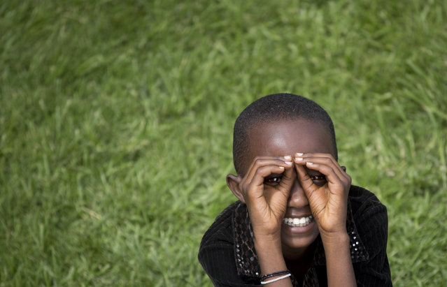 A young Rwandan girl mimics the photographer taking her photograph, at a public ceremony to mark the 20th anniversary of the Rwandan genocide, at Amahoro stadium in Kigali, Rwanda Monday, April 7, 2014. (Photo by Ben Curtis/AP Photo)