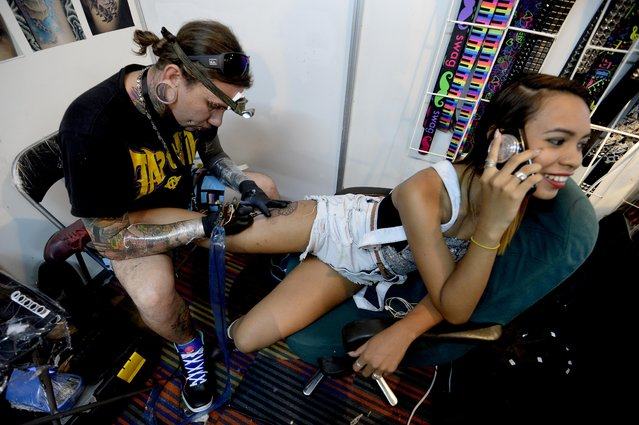 """A tattoo artist works on a woman's leg during the """"Expo Tatoo Venezuela"""" in Caracas on January 29, 2015. (Photo by Federico Parra/AFP Photo)"""