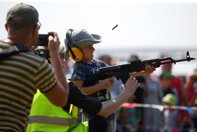 An instructor teaches a boy to shoot a Kalashnikov automatic rifle during the International Army Games 2018, in Alabino, outside Moscow, Russia on July 28, 2018. (Photo by Sergei Karpukhin/Reuters)