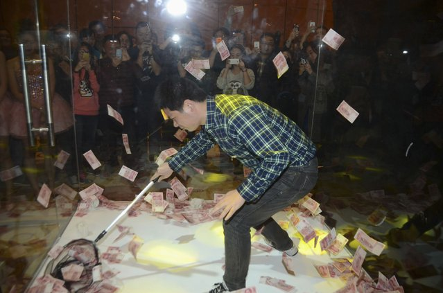 People take pictures and videos as a man (front) nets 100 yuan banknotes in a glass room to win cash prize during a local company's annual celebration before the Chinese Lunar New Year, in Shanghai, January 29, 2015. (Photo by Reuters/Stringer)