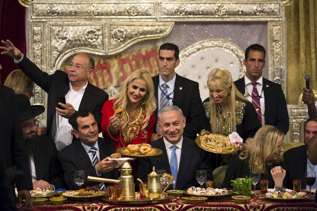 Israeli Prime Minister Benjamin Netanyahu (C) and his wife Sara (R) attend the Mimona ceremony in the Israeli town of Or Akiva near Caesarea April 11, 2015. (Photo by Amir Cohen/Reuters)