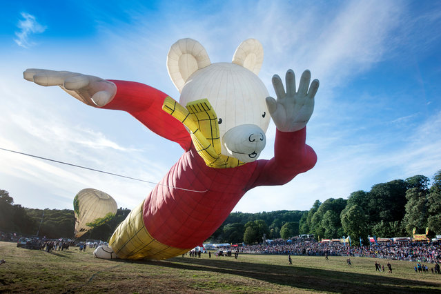 A hot air balloon in the shape of children's comic Rupert Bear is seen tethered before a tethered flight at the Bristol International Balloon fiesta in south west England, Britain, August 10, 2018. (Photo by Adrian Sherratt/The Guardian)