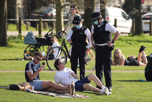 Police officers speak to a man as people enjoy the weather at Clapham Common, in London, Britain on March 30, 2021. (Photo by Tom Nicholson/Reuters)