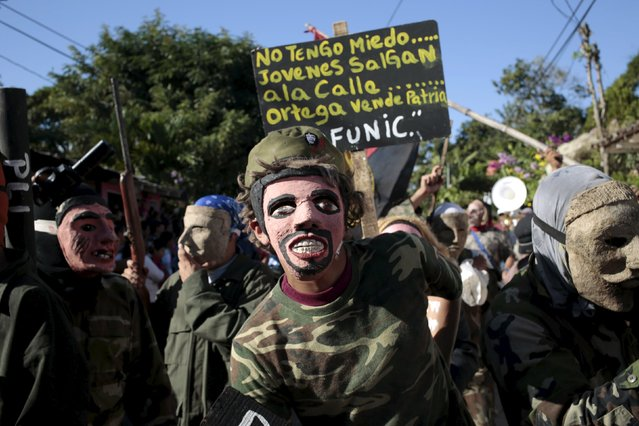 """Men wearing masks and dressed as military members take part in a festival honouring San Silvestre, in the town of Catarina, Nicaragua January 1, 2016. The placard reads, """"I'm not afraid, young people off the streets, Ortega you sell our country"""", in reference Nicaragua's President Daniel Ortega. (Photo by Oswaldo Rivas/Reuters)"""