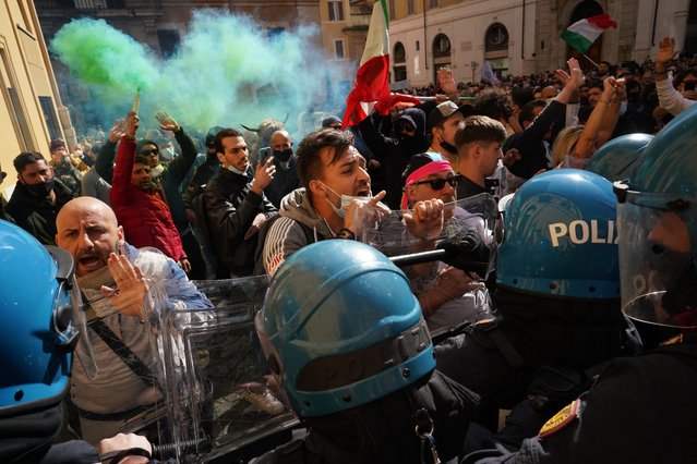 Demonstrators scuffle with Italian Policemen during a protest by Restaurant and shop owners outside the Lower Chamber in Rome, Tuesday, April 6, 2021. Demonstrators demanded to reopen their business and protested against restrictive measures of the Italian Government to cope with the surge of COVID-19 cases. (Photo by Andrew Medichini/AP Photo)