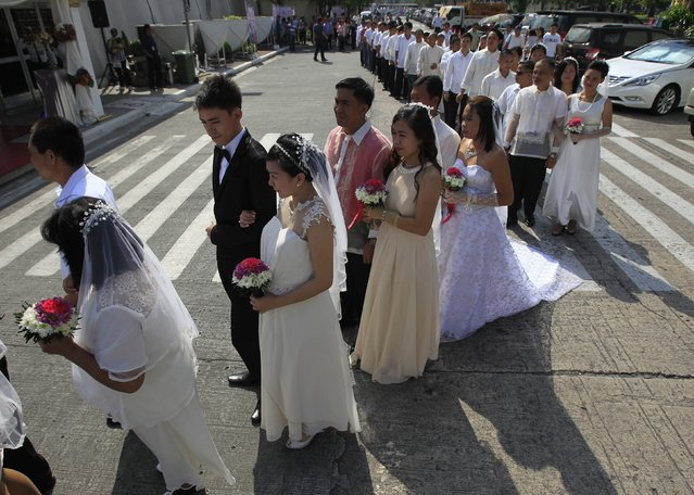 Couples march towards the venue of a mass wedding in Manila February 12, 2015. According to the event's organizers, at least 700 couples tied the knot during a mass wedding on Thursday, which was organized by a government agency as part of early Valentines Day celebrations. (Photo by Romeo Ranoco/Reuters)