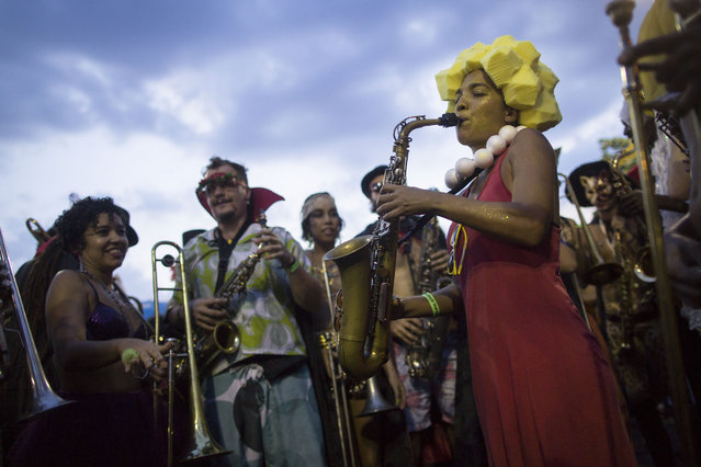 "Revelers listen as a woman plays her saxophone during the ""Bloco Virtual"" carnival parade at Leme Beach in Rio de Janeiro, Brazil, Friday, February 13, 2015. The five days of over-the-top parades and raucous, alcohol-soaked street parties that make up Rio de Janeiro's world-famous Carnival celebrations kicked off Friday. (Photo by Felipe Dana/AP Photo)"