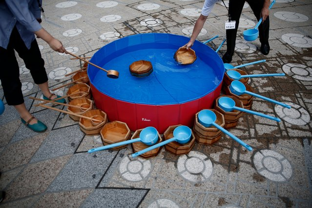 People fill wooden buckets with water during a water sprinkling event called Uchimizu which is meant to cool down the area, in Tokyo on July 23, 2018. (Photo by Martin Bureau/AFP Photo)