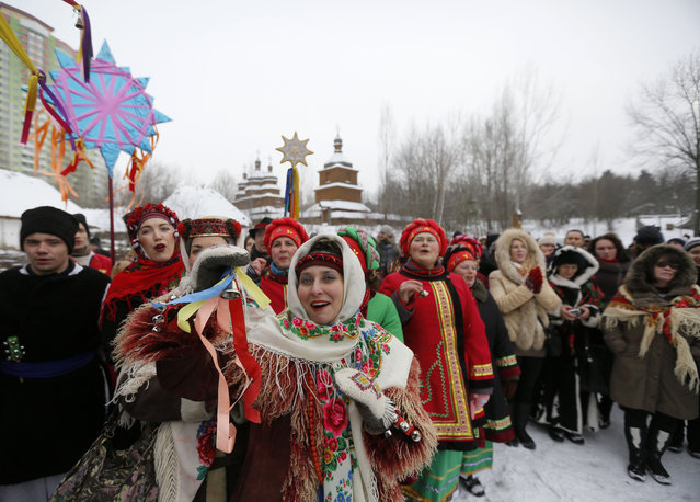 Ukrainians wearing traditional costumes sing Kolyadky or Ukrainian Christmas Carols, as a part of Orthodox Christmas in Kiev, Ukraine, Thursday, January 7 2016. Orthodox Christians mark their traditional Christmas Day Jan. 7, with many ancient symbolic events. (Photo by Sergei Chuzavkov/AP Photo)