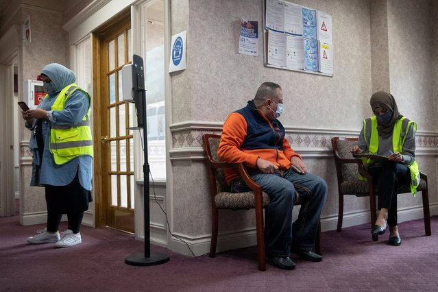 A volunteer assists a man to fill out paperwork before he is vaccinated against the coronavirus at a clinic hosted by the Arab Community Center for Economic and Social Services (ACCESS) in Sterling Heights, Michigan, April 20, 2021. (Photo by Emily Elconin/Reuters)