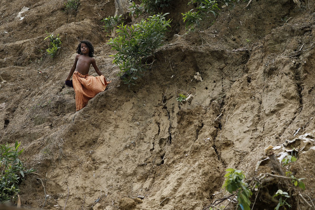 In this  June 27, 2018, photo, a young girl slides down the side of a muddy hill where a landslide which destroyed eight shelters occurred in Chakmarkul refugee camp, Bangladesh. (Photo by Wong Maye-E/AP Photo)