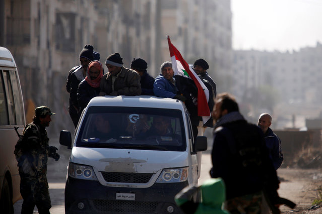 People ride a pick-up truck with a Syrian National flag in goverment controlled Hanono housing district in Aleppo, Syria December 4, 2016. (Photo by Omar Sanadiki/Reuters)