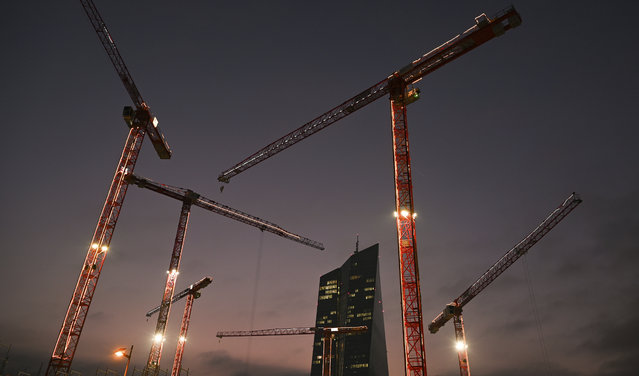 Construction cranes are illuminated by Christmas fairy lights, in the evening light on a construction site near the European Central Bank (ECB) building in Frankfurt, Germany Thursday November 26, 2020. (Photo by Arne Dedert/dpa via AP Photo)