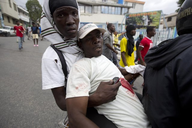 A demonstator is taken to hospital after he was wounded by a shotgun blast during a street protest after it was announced that the runoff Jan. 24, presidential election had been postponed, in Port-au-Prince, Haiti, Friday, January 22, 2016. (Photo by Dieu Nalio Chery/AP Photo)