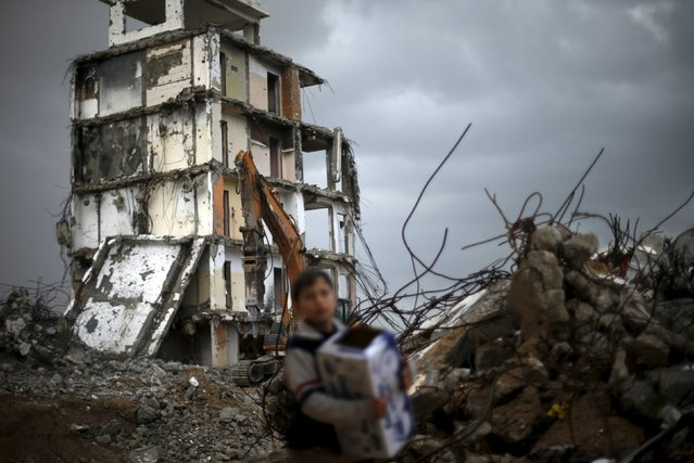 A Palestinian boy walks past a residential building destroyed during the 2014 war, on a rainy day in Beit Hanoun in the northern Gaza Strip January 25, 2016. (Photo by Suhaib Salem/Reuters)