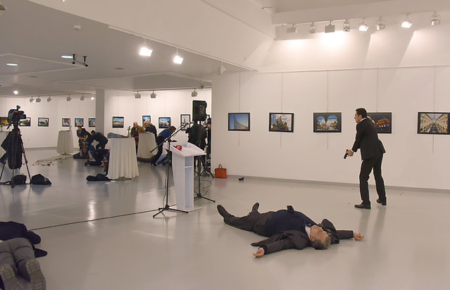 "This picture taken on December 19, 2016 shows Andrey Karlov (2ndR), the Russian ambassador to Ankara, lying on the floor after being shot by a gunman (R) during an attack during a public event in Ankara. A gunman crying ""Aleppo"" and ""revenge"" shot Karlov while he was visiting an art exhibition in Ankara on December 19, witnesses and media reports said. The Turkish state-run Anadolu news agency said the gunman had been ""neutralised"" in a police operation, without giving further details. (Photo by AFP Photo/Stringer)"