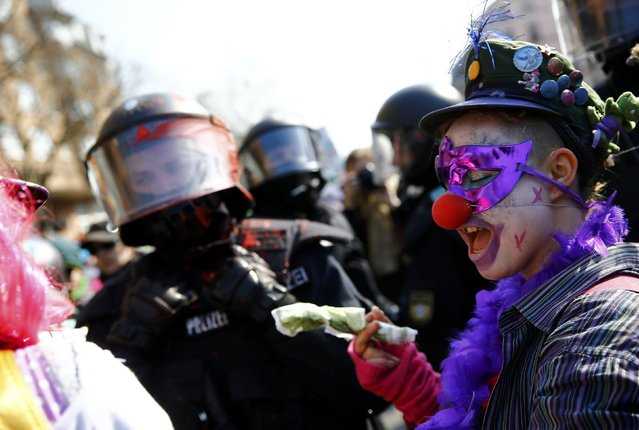 An anti-capitalist protester dressed as a clown gestures in front of a policeman near the European Central Bank (ECB) building before the official opening of its new headquarters in Frankfurt March 18, 2015. (Photo by Kai Pfaffenbach/Reuters)