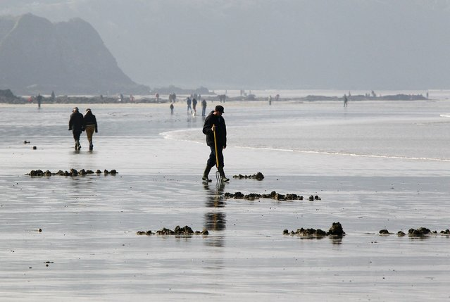 A man digs for shellfish during a record low tide on Kerlaz beach near Douarnenez in western France, March 21, 2015. (Photo by Mal Langsdon/Reuters)