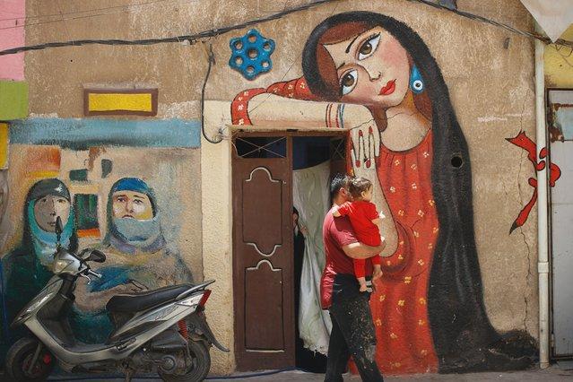 Artist Ali Khalifa, center, draws graffiti at his old Kadhimiya district of Baghdad that needed municipal services, Iraq, Wednesday, June 2, 2021. (Photo by Hadi Mizban/AP Photo)